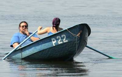 fat man having a fag being rowed by woman